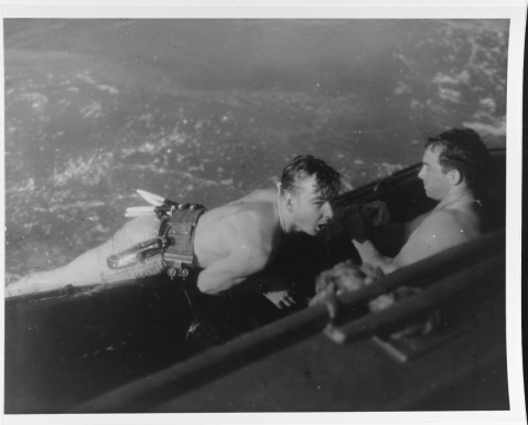 Recovery of a UDT swimmer, using a rubber raft towed alongside a power boat. Note swimmer's life belt, sheath knife and other equipment. Photo released 31 August 1945. It may have been taken during the Balikpapan operation early in July. 80-G-274683