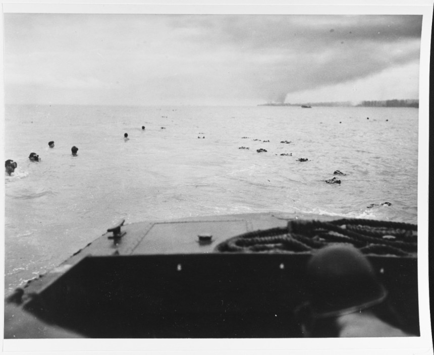 UDT swimmers prepare to recover their gear and swim towards their objective area, after being dropped off by a landing craft. Photograph released circa 31 August 1945. It may have been taken during the Balikpapan Invasion that July. 80-G-274690