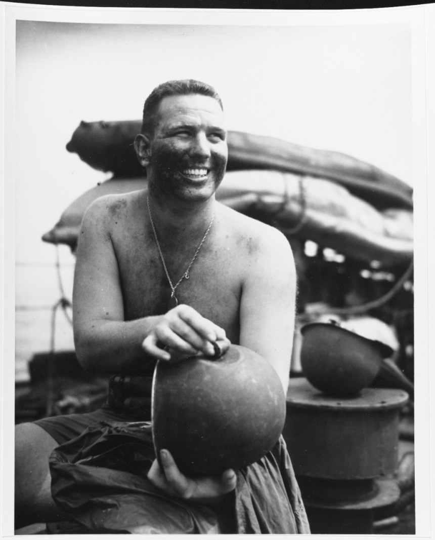 Ensign S.E. Lanier holds the nose of a Japanese 37mm shell which hit, but did not pierce, his helmet. Photographed released 31 August 1945. It may have been taken during the Balikpapan Invasion, early that July. 80-G-274691