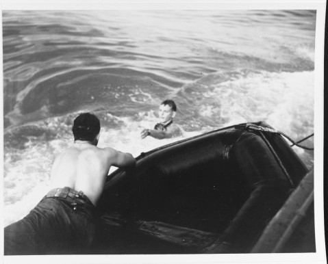 Underwater demolition swimmer prepares for pickup, after he had completed his work off the Balikpapan beaches, 3 July 1945. Pickup boat is a rubber raft towed alongside a powerboat. Photographed by Lieutenant Junior Grade C.F. Waters. 80-G-274701