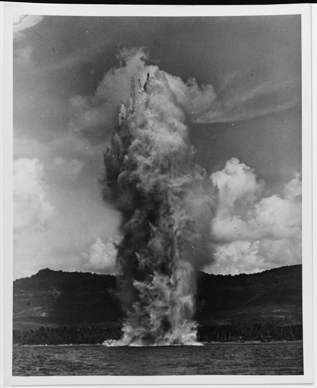 A UDT (Underwater Demolition Team) explosive charge blows up an underwater obstacle off Agat Beach, Guam, during the invasion of that island, July 1944 80-G-700639