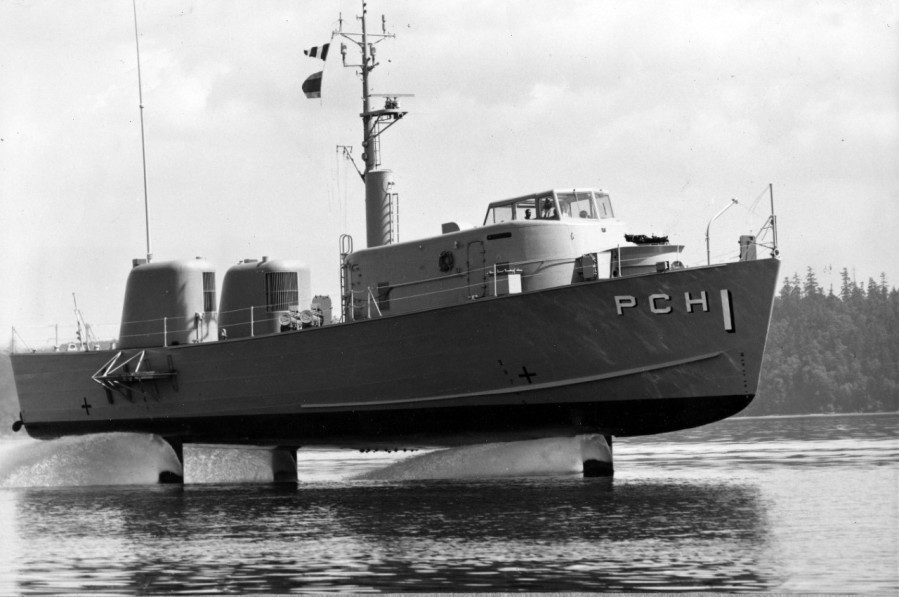 """Flying"" above the surface of Puget Sound, the United States Navy's first patrol craft - hydrofoil, USS High Point (PCH-1), demonstrates the lift capability of her wholly submerged, wing-like foils. The submarine chased is designed for speeds in excel of 50 miles an hour (80 km-h) and, with an automatic control system closely akin to an airplane's autopilot, provides a swift and stable platform in seas virtually as high as the length of its foil struts. July 5, 1963. Accession #: L45 Catalog #: L45-125.04.04"