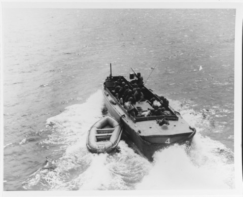 An underwater demolition team's LCPR leaves its fast transport (APD), towing a rubber boat, 3 July 1945. This shows the way the rubber boat is positioned for UDT swimmer discharge and pickups. Photographed by Lieutenant Junior Grade C.F. Waters. 80-G-274700