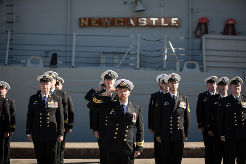 Lieutenant Commander Nick Graney salutes during the national anthem as part of HMAS Newcastle's decommissioning ceremony at Fleet Base East, Sydney on Sunday 30th June 2019.