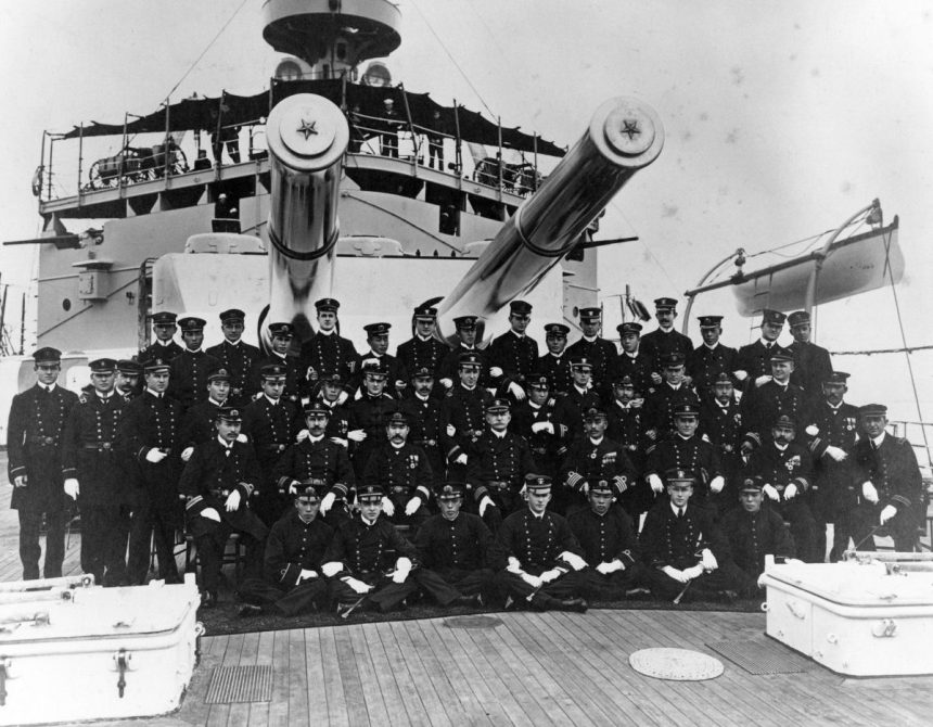"Stern 8""/45 (20.3 cm) turret on armored cruiser Nisshin on 24 October 1908. Ship's officers with USN officers from USS Missouri (B-11) during ""Great White Fleet"" around the world cruise. Note the landing guns on the upper platform. U.S. Naval Historical Center Photograph # NH 82511."