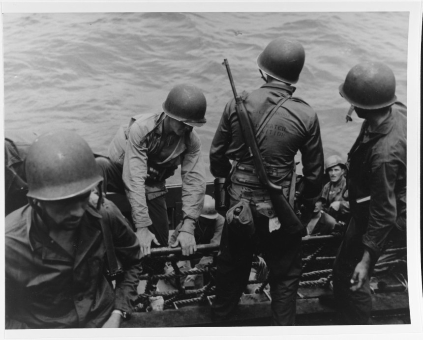 Underwater demolition team members boarding a landing craft off Saipan. Note belt equipment, life belt equipment, life belt and M-1 carbine of man in right center. His shirt indicates that he is a member of UDT-6. Photographed by Commander Bonnie Powell. 80-G-274665