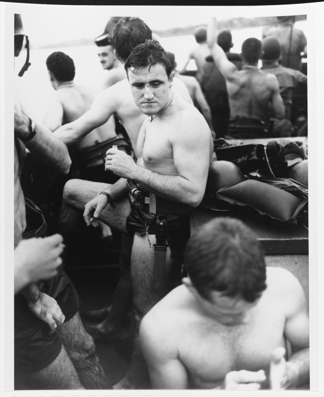 Underwater demolition swimmer, SF1c John Regan gets a drink and smoke after setting charges off Balikpapan, circa early July 1945. Note his sheath knife 80-G-274698