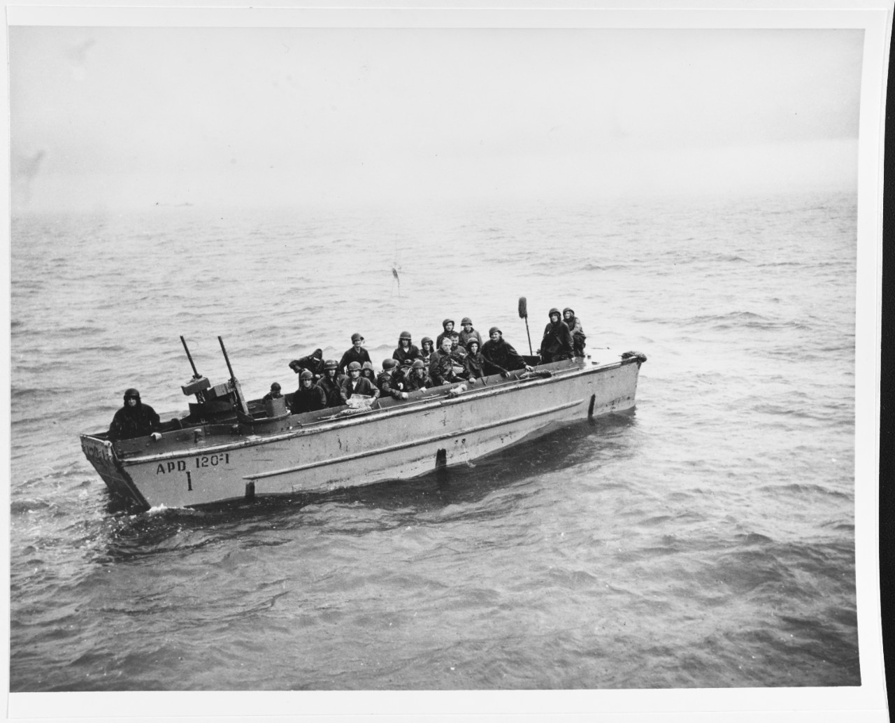 """Underwater demolition team swimmers wait in the rain to be taken aboard their fast transport, off Balikpapan, 3 July 1945. The swab mounted on the stern of their LCP(R) means """"Clean sweep, day's work done"""". They are watching casualties going aboard from another LCP(R). Boat is from USS KLINE (APD-120). Photographed by Lieutenant Junior Grade C.F. Waterman. 80-G-274686"""