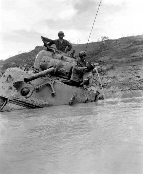 """A tank sunk in 5 feet of water waits for towing equipment. The Tank Commander gives vent to his feelings with a string of unprintable phraseology, while his driver uses a helmet to bale out the interior. Okinawa."""
