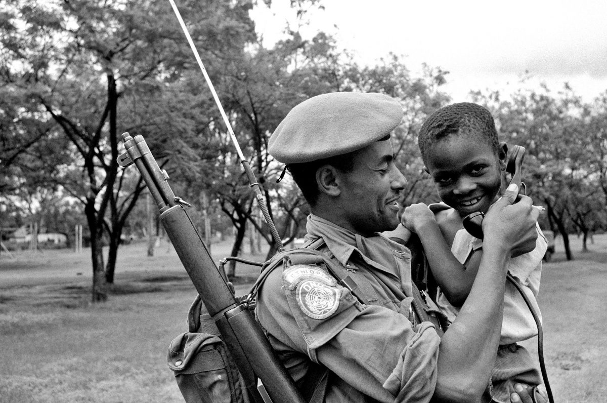 A Congolese child is seen in the arms of an Ethiopian soldier, listening over a field telephone, Katanga, 1 March 1963. Note his M1 Garand